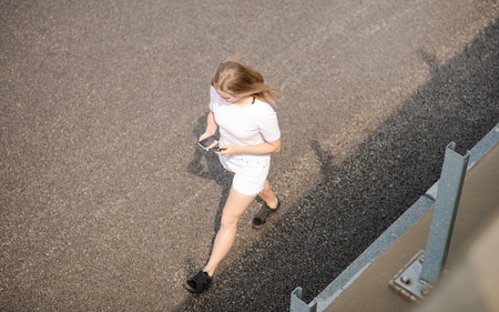 Young Beautiful Blonde Girl Using Smartphone while Walking on the Road