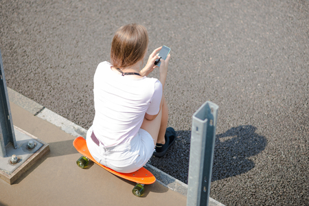 Young Beautiful Blonde Girl Using Smartphone while Sitting on the Skateboard