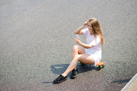Young Beautiful Smiling Girl Making Selfie with Smartphone while Sitting on the Skateboard on the Road