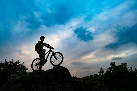 Silhouette of Cyclist with Mountain Bike on the Rock at Sunset. Extreme Sports and Enduro Cycling Concept. Stock Photo
