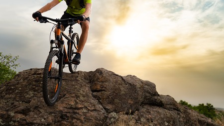 Cyclist Riding the Mountain Bike Down the Rock on the Sunset Sky Background. Extreme Sport and Enduro Biking Concept.