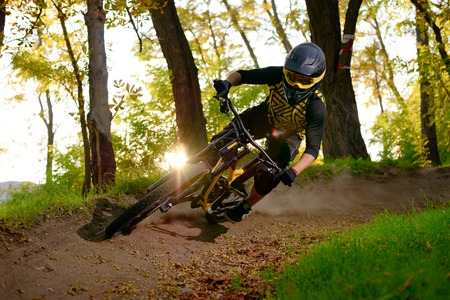 Professional DH Cyclist Riding the Mountain Bike on the Autumn Forest Trail at Sunset. Extreme Sport and Enduro Cycling Concept. Stock Photo