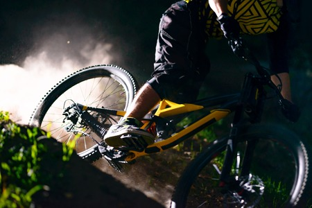 Professional DH Cyclist Riding the Mountain Bike on the Forest Trail at Night. Extreme Sport and Enduro Cycling Concept. Stock Photo