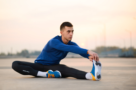 Young Male Runner Stretching and Preparing for Run at Sunset. Healthy Lifestyle and Sport Concept.