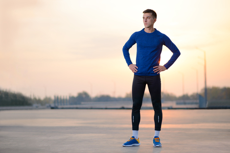 Young Male Runner Resting after Run at Sunset. Healthy Lifestyle and Sport Concept.