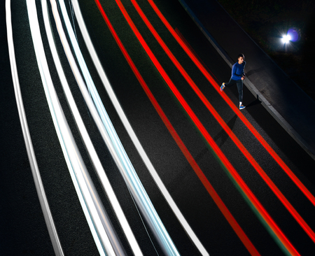 Young Sports Man Running on the Night Road with Cars Light Trails. Healthy Lifestyle and Urban Sport Concept. Stock Photo