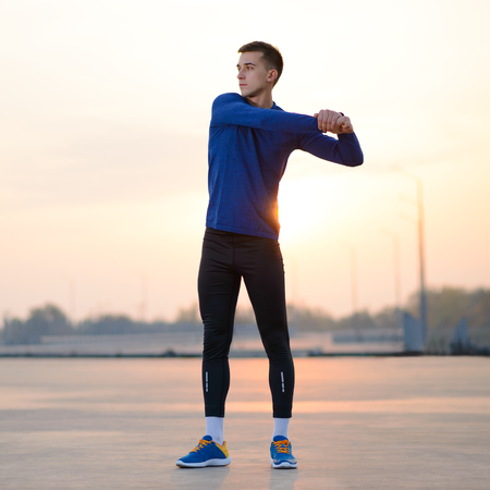 Young Male Runner Stretching Before Run at Sunset. Healthy Lifestyle and Sport Concept.