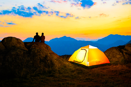 Young Couple Sitting on the Rock near Illuminated Tent and Watching the Beautiful Evening Mountain View with Sunset Sky Stock Photo