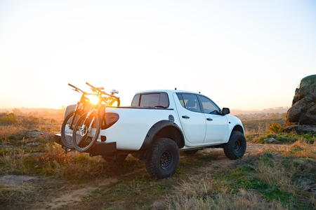 Pickup Offroad Truck with Bikes in the Body in the Mountains at Sunset. Adventure and Car Travel Concept. Stock Photo