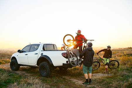 Friends Taking MTB Bikes off the Pickup Offroad Truck in Mountains at Sunset. Adventure and Travel Concept. Stock Photo