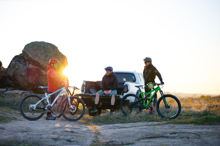 Friends are Resting on Pickup Offroad Truck after Bike Riding in the Mountains at Sunset. Adventure and Travel Concept Stock Photo