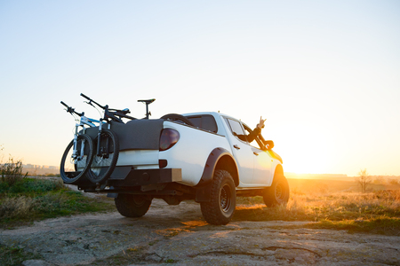 Friends Driving Pickup Offroad Truck in the Mountains with Bikes in the Body at Sunset. Adventure and Travel Concept.