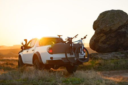 Friends Driving the Pickup Offroad Truck in the Mountains with Bikes in the Body at Warm Autumn Sunset. MTB Adventure and Car Travel Concept. Stock Photo