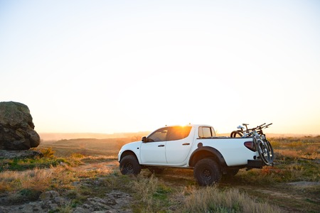 Pickup Offroad Truck with MTB Bikes in the Body in the Mountains at Warm Autumn Sunset. Cycling Adventure and Car Travel Concept. Stock Photo
