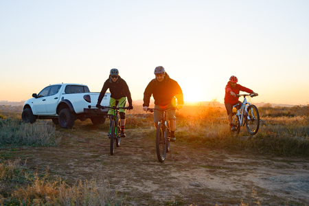 Friends Riding Bikes in the Mountains in front of the Pickup Off Road Truck at Sunset. Adventure and Travel Concept
