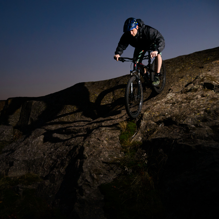 Cyclist Riding the Bike on Rocky Trail at Night. Extreme Sport and Enduro Biking Concept.