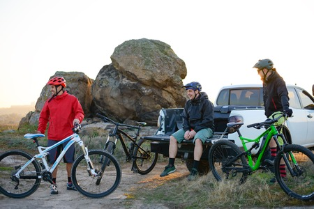 Friends Resting near Pickup Off Road Truck after Bike Riding in the Mountains at Sunset. Adventure and Travel Concept.