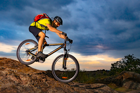 Cyclist Riding the Mountain Bike on Rocky Trail at Sunset. Extreme Sport and Enduro Biking Concept. Reklamní fotografie