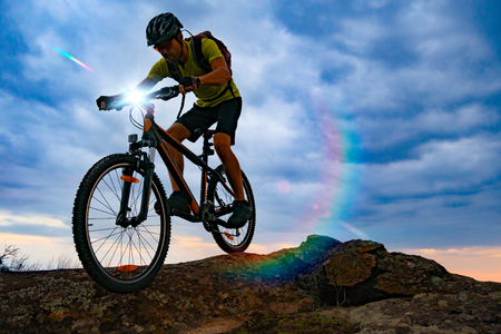 Cyclist Riding the Mountain Bike on Rocky Trail at Sunset. Extreme Sport and Enduro Biking Concept. Banco de Imagens