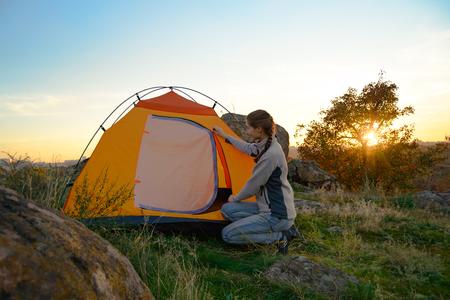 Junge Frau, die das Zelt bei Sonnenuntergang in den Bergen zusammenbaut. Abenteuer- und Reisekonzept.