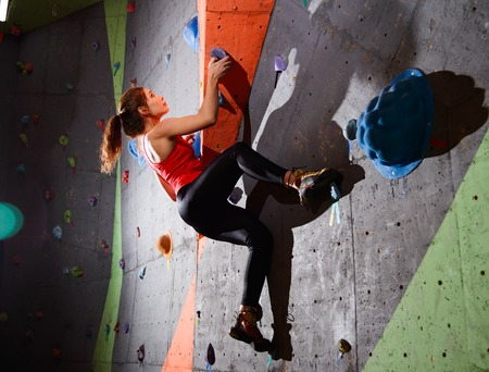 Young Active Woman Bouldering on Colorful Artificial Rock in Climbing Gym. Extreme Sport and Indoor Climbing Concept Imagens