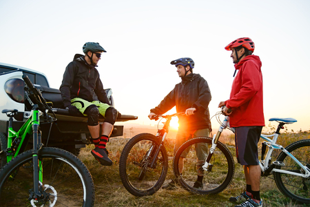Friends Cyclists Resting near the Pickup Off Road Truck after Enduro Bike Riding in the Mountains at Warm Autumn Sunset. MTB Adventure and Car Travel Concept.