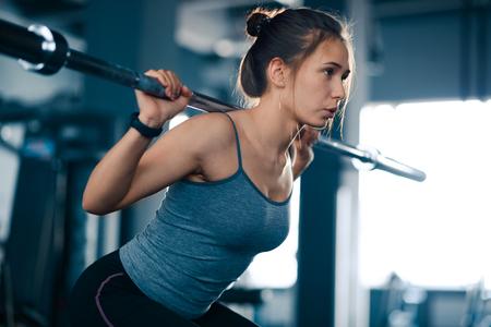 Attraente giovane donna sportiva facendo squat con bilanciere in palestra. Fitness e stile di vita sano.