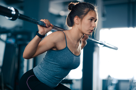 Mujer atractiva joven deportes haciendo sentadillas con barra en el gimnasio. Fitness y estilo de vida saludable.