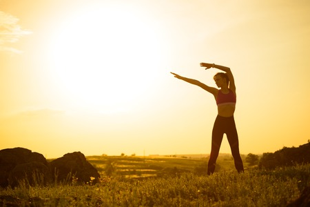 Woman Doing Stretching Outdoor. Warm up Exercise Against Sunset. Sport and Healthy Active Lifesyle Concept. Reklamní fotografie