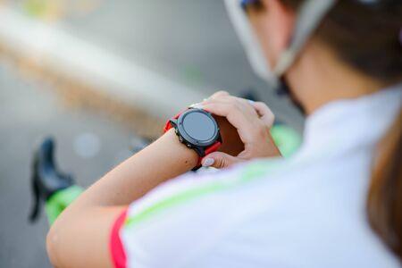 Jeune femme avec vélo de route à l'aide de Smartwatch au coucher du soleil. Gros plan de la main avec Fitness Tracker. Concept sportif d'entraînement.