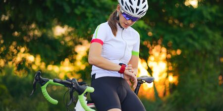 Young Woman with Road Bicycle Using Smartwatch at Sunset. Closeup of Hand with Fitness Tracker. Training Sports Concept.