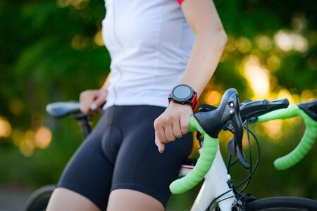 Multisport Smartwatch on the Hand of Road Cyclist Resting with Bicycle at Sunset. Closeup of Hand with Fitness Tracker. Banque d'images