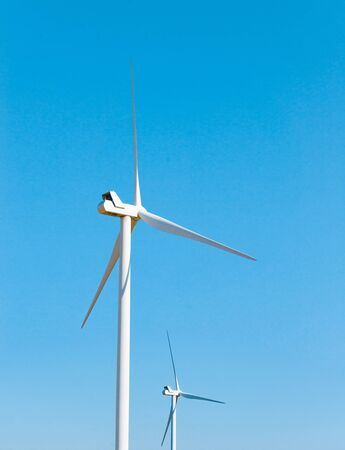 Wind Generator Turbine on the Clear Blue Sky Bacground. Green Renewable Energy Concept. Stock Photo