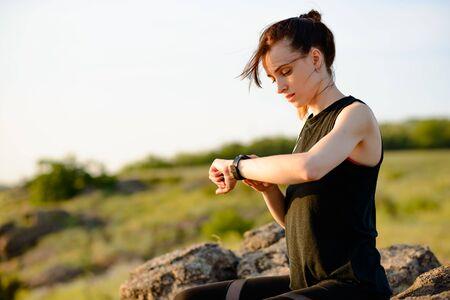 Coureur de jeune femme à l'aide de Smartwatch multisport au Sunset Trail. Gros plan de la main avec Fitness Tracker. Concept sportif.