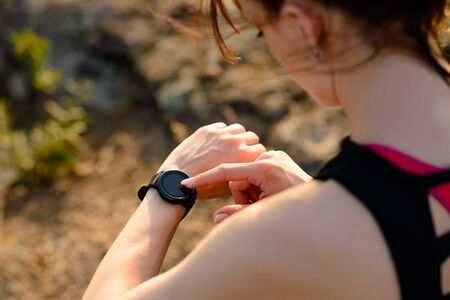 Young Woman Runner Using Multisport Smartwatch at Sunset Trail. Closeup of Hand with Fitness Tracker. Sports Concept.