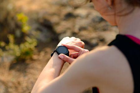 Coureur de jeune femme utilisant une montre intelligente multisports au coucher du soleil sur le sentier de la montagne. Gros plan des mains avec Fitness Tracker. Concept d'entraînement et de sport.