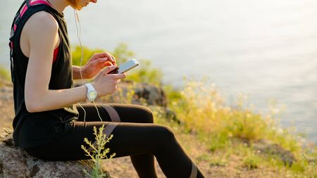 Young Woman Runner Using Smartphone and Listening to Music at Sunset on the Mountain Trail. Sports Concept.