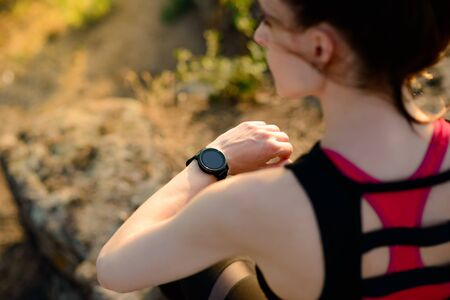 Young Woman Runner Using Multisport Smartwatch at Sunset on the Mountain Trail. Closeup of Hands with Fitness Tracker. Training and Sports Concept. Banque d'images