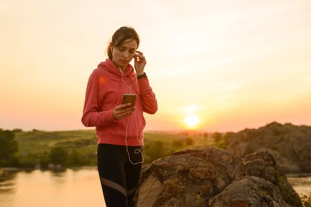Young Woman Runner Resting after Workout, Using Smartphone and Listening to Music at Sunset on the Mountain Trail. Training and Sports Concept. Banque d'images
