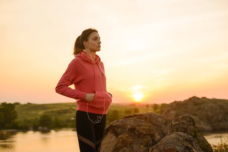 Young Woman Runner Resting after Workout and Listening to Music at Sunset on the Mountain Trail. Training and Sports Concept.