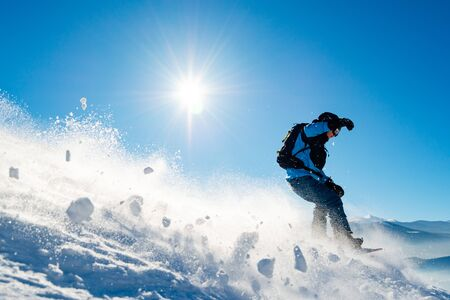Snowboarder Riding Snowboard in Mountains at Sunny Day. Snowboarding and Winter Sports