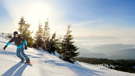 Young Snowboarder Riding Red Snowboard in the Mountains at Sunny Day. Snowboarding and Winter Sports