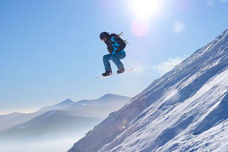 Snowboarder springen op het rode snowboard in de bergen in heldere zonnestralen. Snowboarden en Wintersport