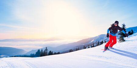 Snowboarder Riding Red Snowboard auf der freien Piste in den schönen Morgenbergen bei sonnigem Wetter. Snowboarden und Wintersport Standard-Bild