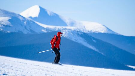 Woman Skier in Red Skiing on the Free Slope in the Beautiful Mountains at Sunny Weather. Skiing and Winter Sports