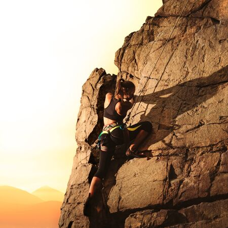 Woman Climber Climbing to the Top of the Rock at Foggy Sunset in the Mountains. Adventure and Extreme Sport Concept