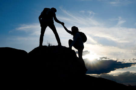 Couple of Young Happy Travelers with Backpacks Hiking in the Mountains at Warm Summer Sunset. Man Helping Woman to Climb to the Top of the Rock. Family Travel and Adventure Concept. Stockfoto