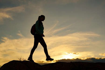 Young Woman Traveler Hiking with Backpack on the Beautiful Rocky Trail at Warm Summer Sunset. Travel and Adventure Concept. Standard-Bild