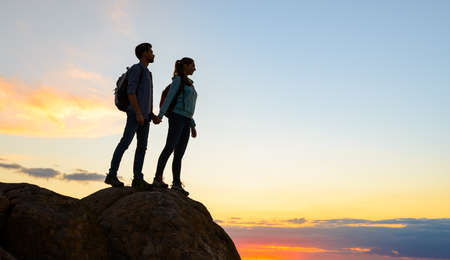 Couple of Young Travelers Standing on the Top of the Rock at Summer Sunset. Family Travel and Adventure Concept Imagens