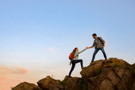 Travelers Hiking in the Mountains at Sunset. Man Helping Woman to Climb to the Top. Family Travel and Adventure. Standard-Bild